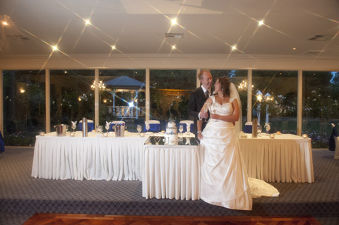 A bride and groom in fornt of their main bridal table at bram Leigh receptions