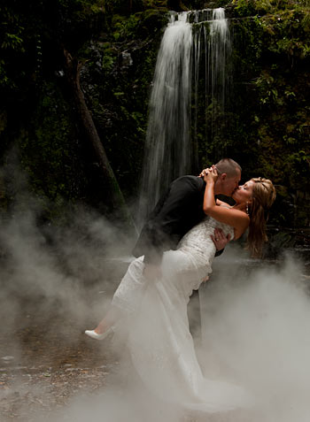 Waterfall Wedding Photography-the team from Wedding Photographers Melbourne feature a bridal couple enjoying a waterfall in a rainforest setting.