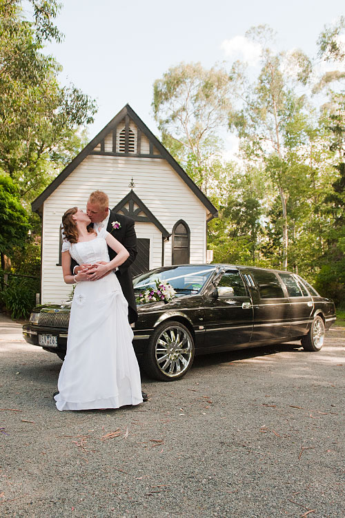 bridal couple outside chapel with stretch limousine