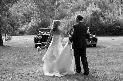 black and white wedding photo of limousine with bride and groom walking away
