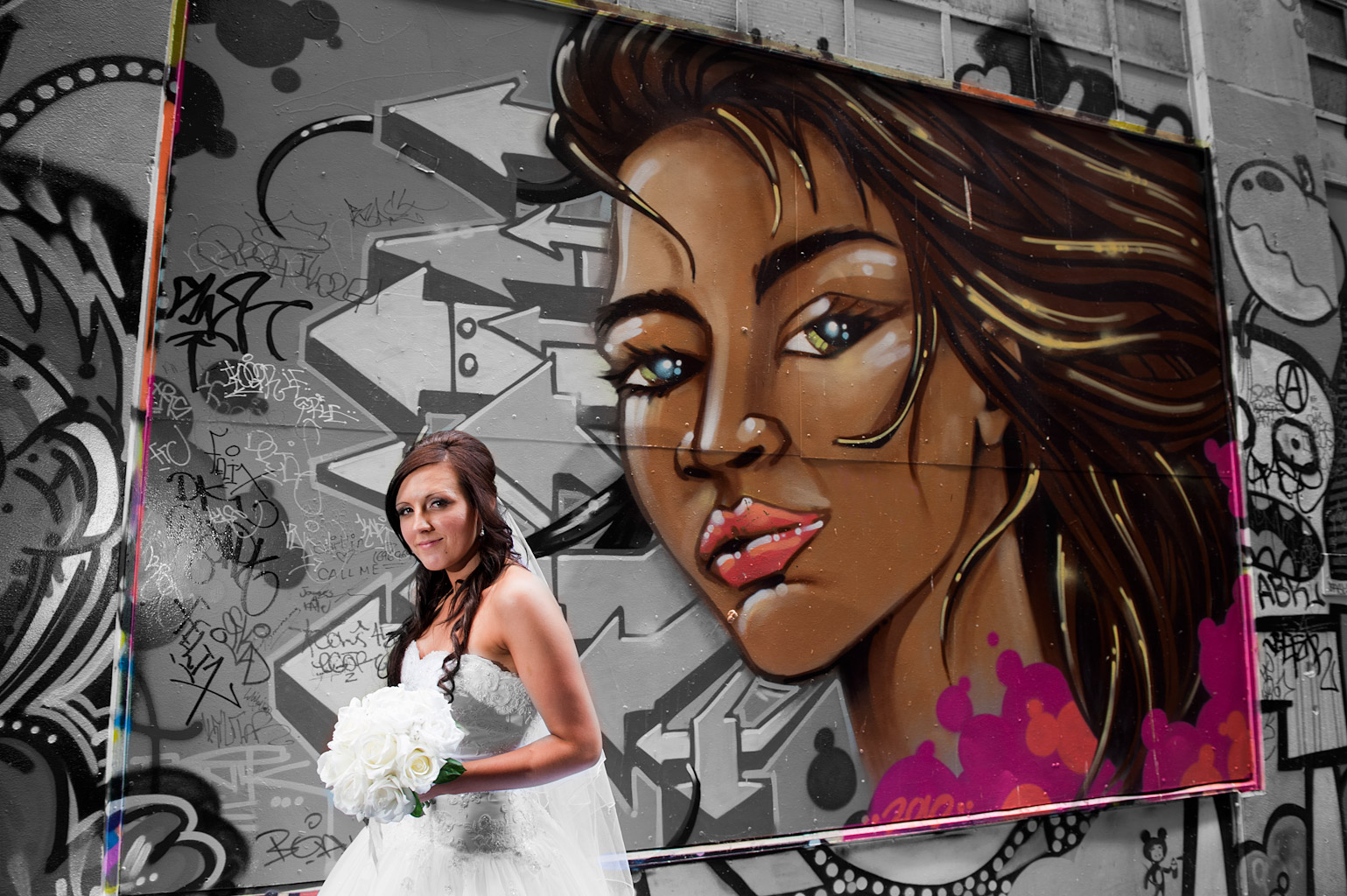 wedding portrait of bride with a background of street art