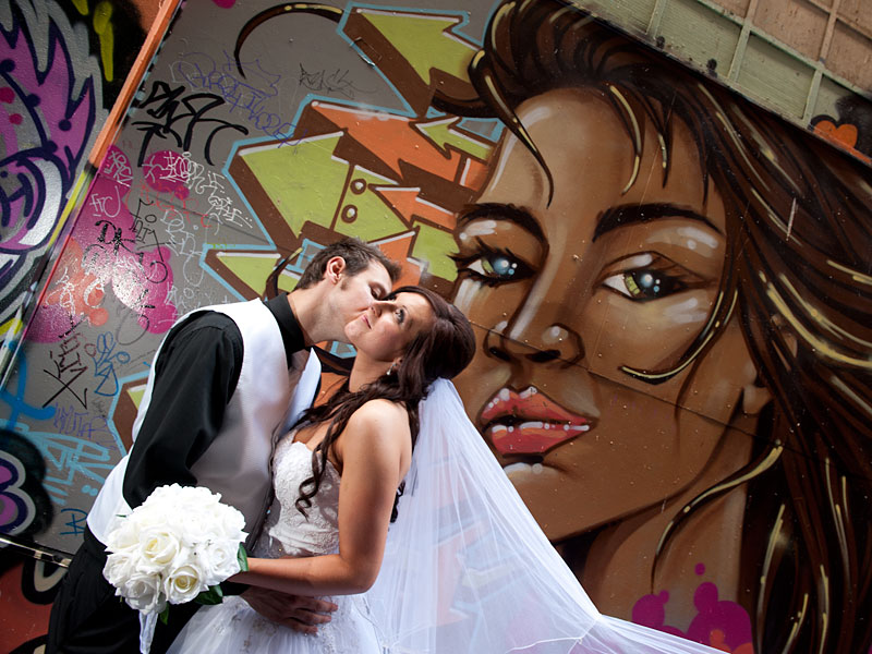 Wedding photography of newlyweds in graffiti alley