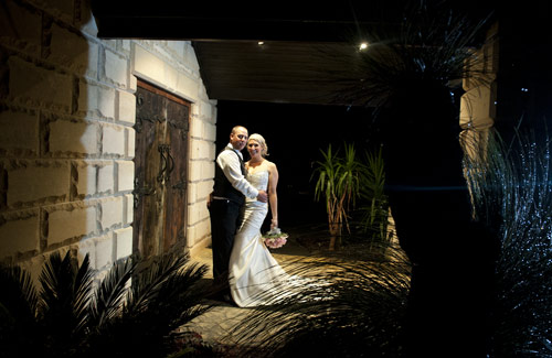 night wedding photography showing forest edge main entrance door, with bridal couple