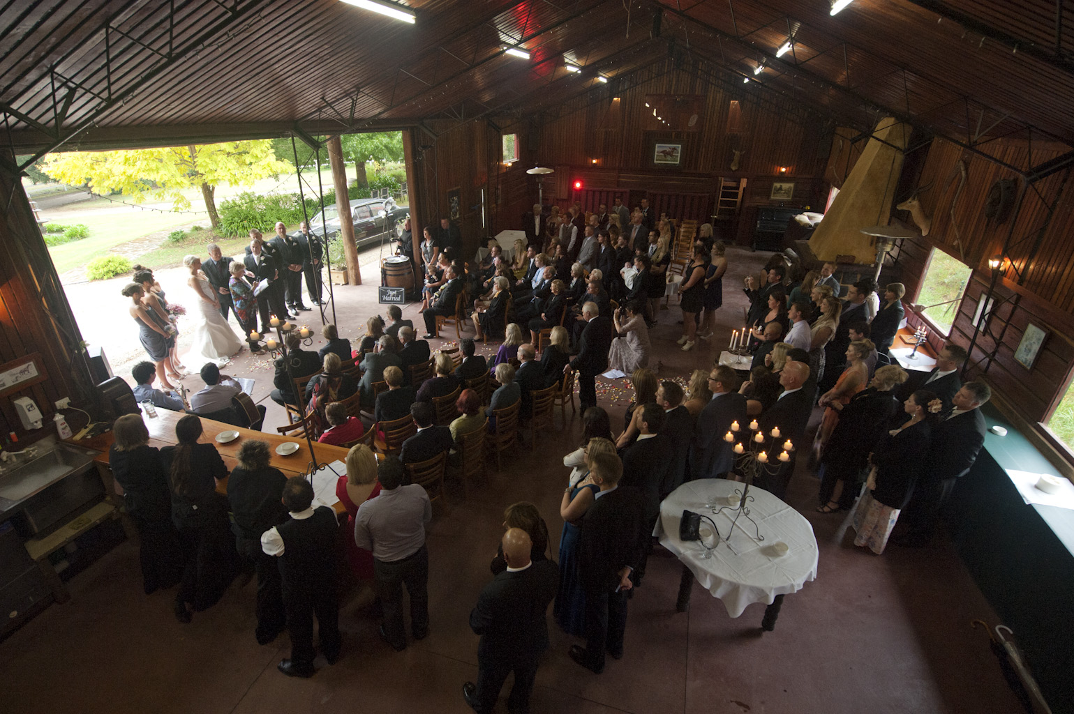 Wedding Photographyof a ceremony taking place in a barn, at forest edge