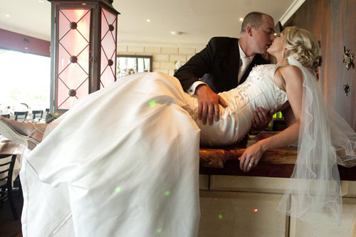 Bride and groom kissing passionately on the bar at Forest Edge Gembrook