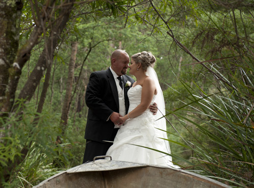Wedding Photography showing an old hull in the forest with a bride and groom embraced