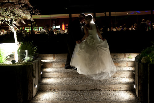 A bride walks up the stairs at night in the Forest Edge garden