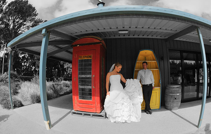 wedding photo showing bride and groom in old red phone box