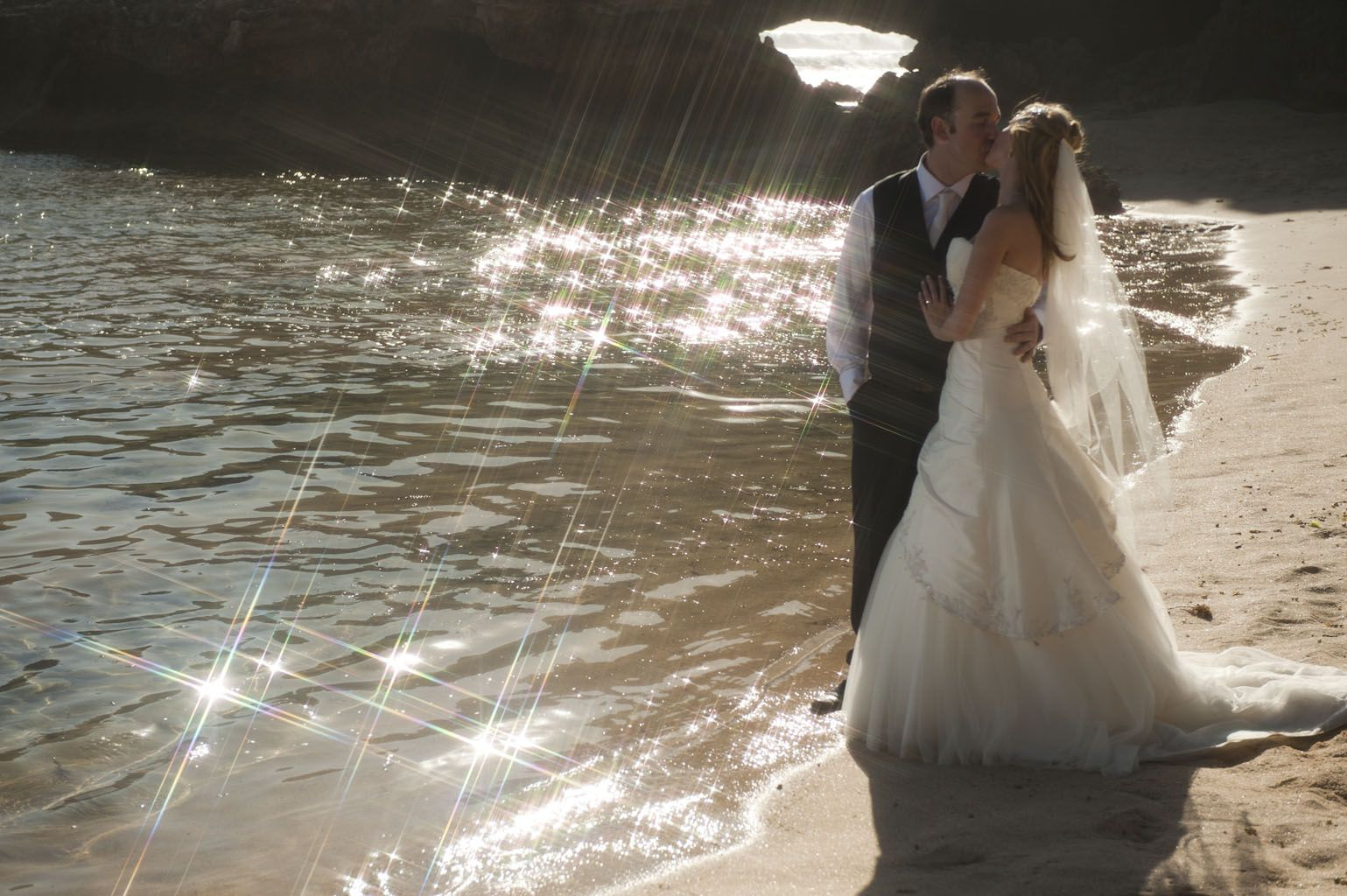 A portrait by wedding photographers melbourne, showing newlyweds by the sparkling waters of a Mornington Peninsula beach, Australia.