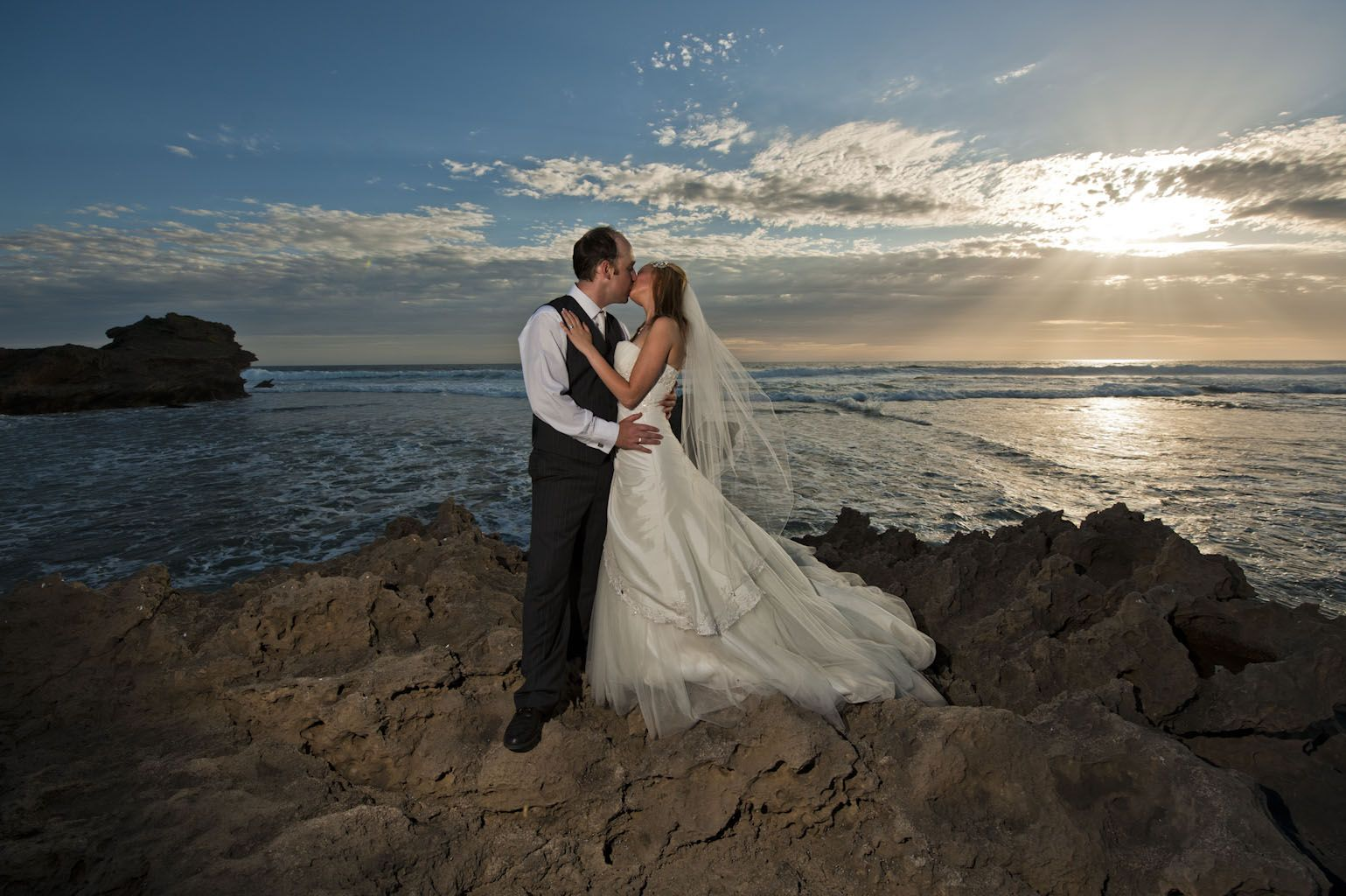 A bride and groom are shown with a beautiful sunset on an ocean beach.