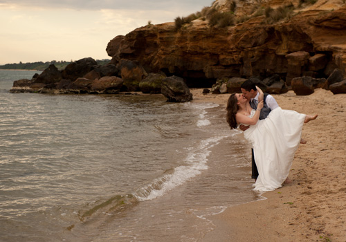 The groom holds the bride in his arms in this Melbourne bridal photographer image of a beach wedding