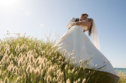 A bridal couple kiss on the foreshore of a Melbourne seaside park