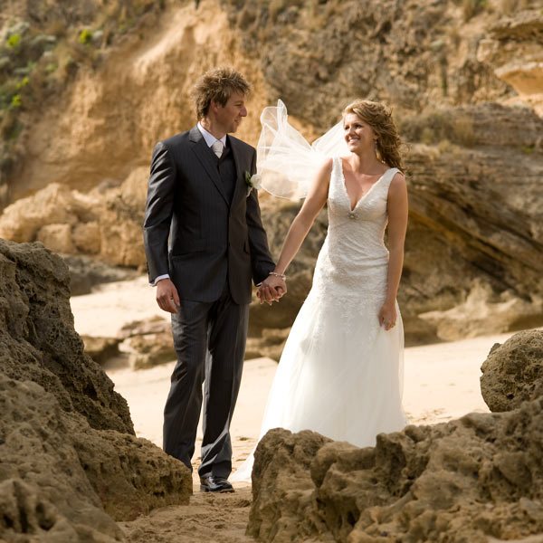 Melbourne wedding photographer image of newlyweds framed by hole in sandstone at Ocean backbeach