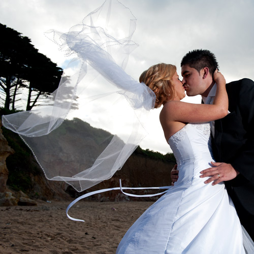Wedding photography Melbourne showing wind blown veil during a kiss