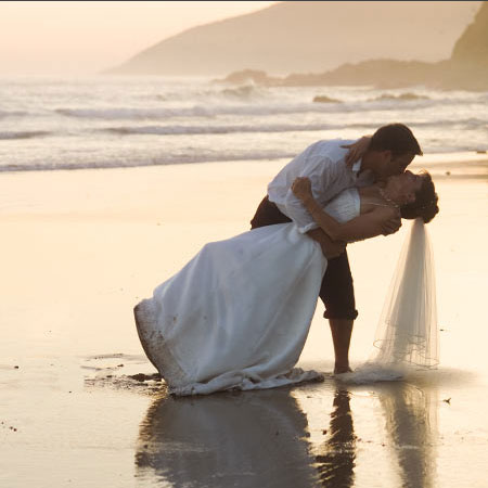 Wedding photography Melbourne beach at sunset, with groom kissing his bride