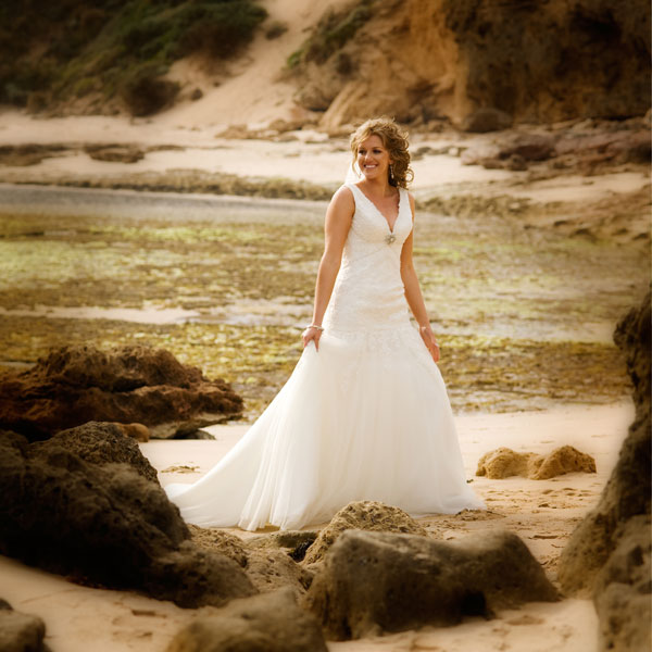 Spectacular ocean cliffs form a backdrop for this bridal portrait