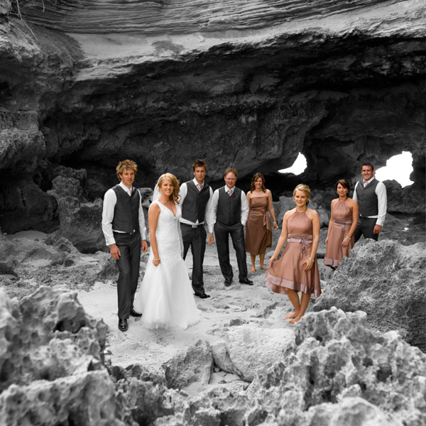 Wedding Photography at a windswept Melbourne ocean beach, with bridal party framed by sandstone cliffs.