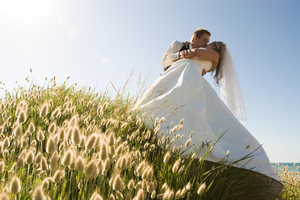 A bridal couple kiss on the foreshore of a Melbourne beach, with grass in the foreground