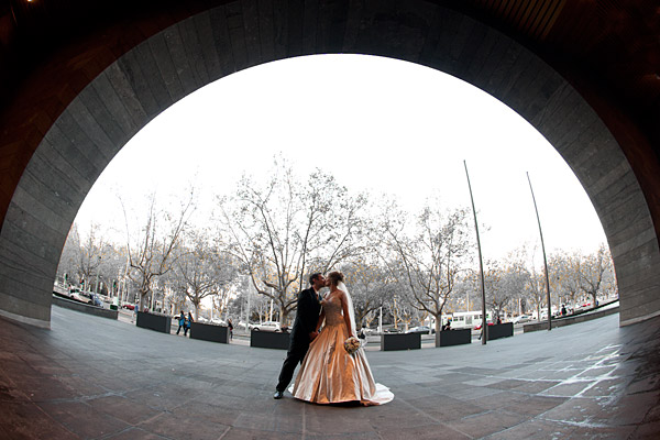 A Melbourne Wedding Photographers image showing an artistic composition of a bridal couple framed by an arch, taken in the Arts Precinct of St Kilda Rd Melbourne Australia.