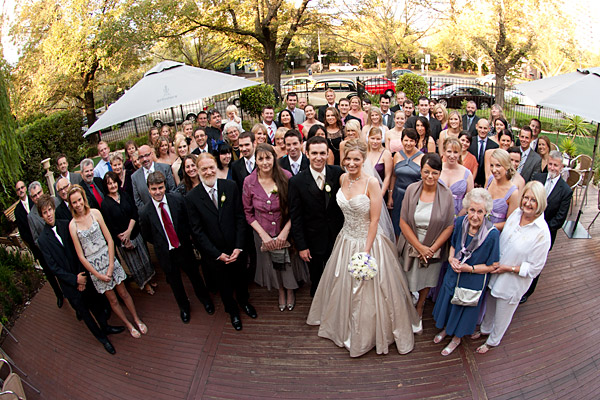 This photo by Melbourne Wedding Photographers Wilderness Images Studio depicts the complete group at a wedding on the courtyard of The Willows Restaurant in St Kilda Rd South Melbourne, Australia.