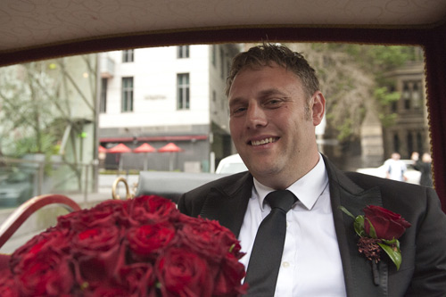 in horse drawn carriage groom with red roses