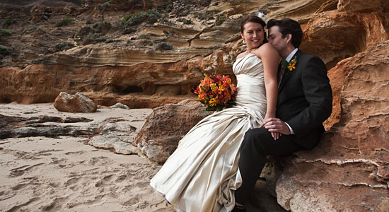 Wedding Photography at a windowspt Melbourne ocean beach, with a bridal couple and sandstone cliffs.
