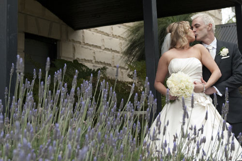 bride and groom kiss, lavender frames foreground