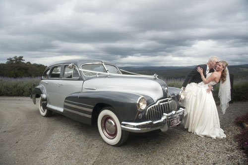 old silver buick wedding car adds to image of newlyweds kissing