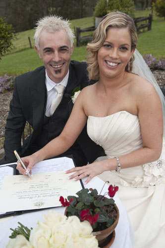 wedded couple sign the registry at forest edge