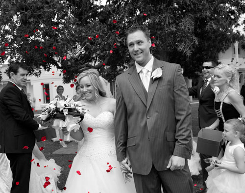 Black and White wedding photo with red rose petals